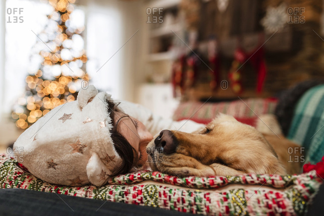 Young girl laying on couch with a dog in a room with a Christmas tree