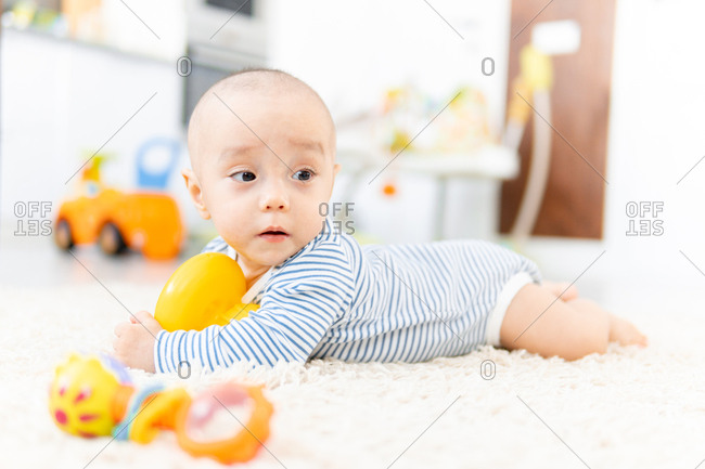 Baby boy crawling on fuzzy carpet holding toy