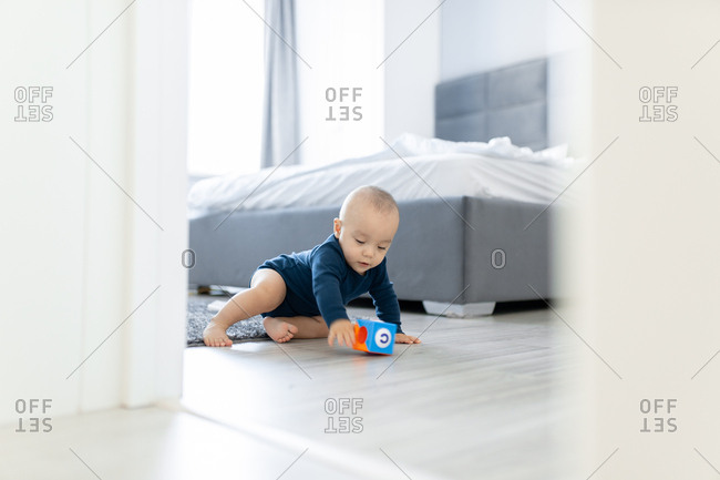 Young boy playing with a toy on a bedroom floor