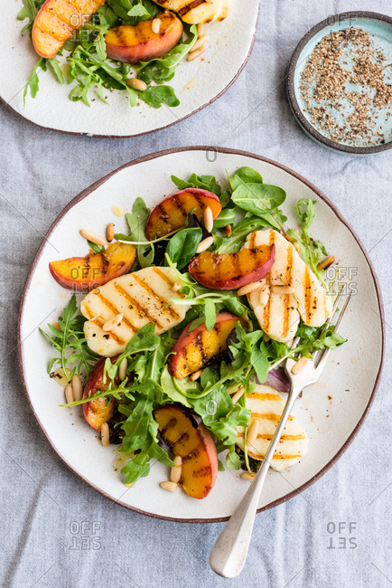 Grilled halloumi and peach salad with fresh rucola and pine nuts