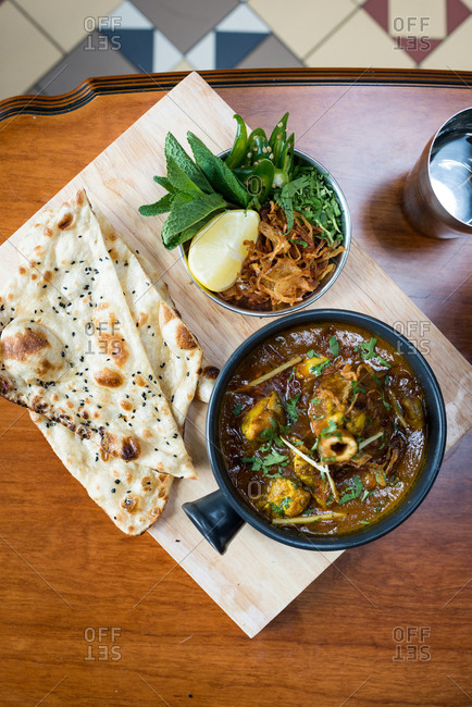 Indian lamb curry with naan bread and fresh herbs