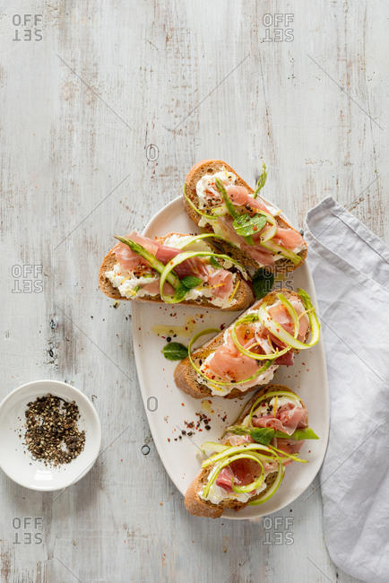 Crostini with ricotta, parma ham, fresh asparagus, mint and black pepper