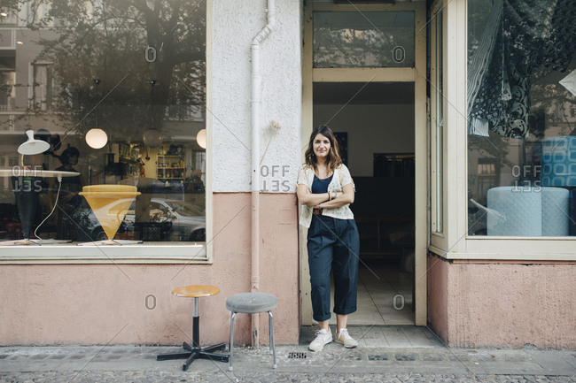 Portrait of confident female craftsperson standing at workshop entrance