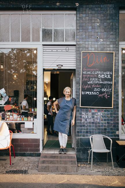 Portrait of female owner standing at entrance of deli