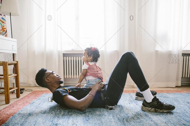 Baby girl sitting on father lying at home