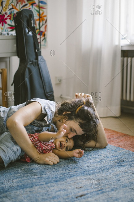 Mother kissing daughter lying on carpet at home