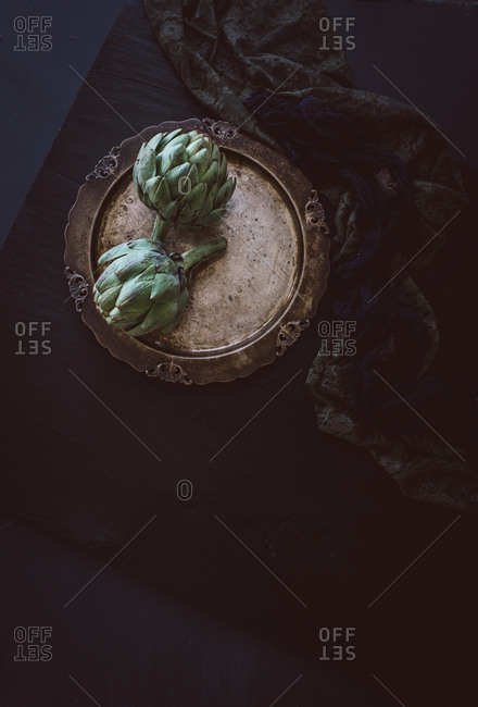 Two artichokes on a plate on a black background
