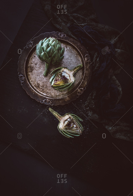 Two artichokes on a plate whole and cut in half