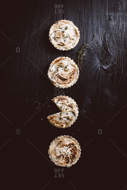 Four miniature blood orange meringue tarts on black background