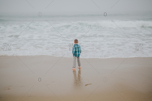 Boy running on a sandy beach in California