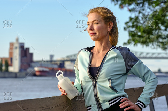 Female athlete having a water break watching sunset, Montreal, Quebec, Canada