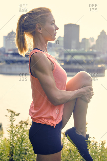 Female athlete stretching leg before running along bike path in park, Montreal, Quebec, Canada