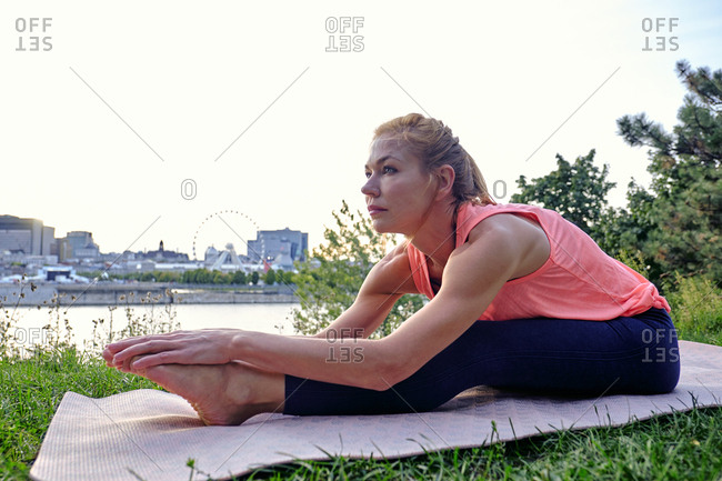 Female athlete doing yoga move in park, Montreal, Quebec, Canada