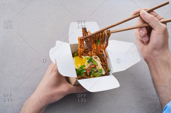 Person eating Asian noodle dish with egg from take-out container