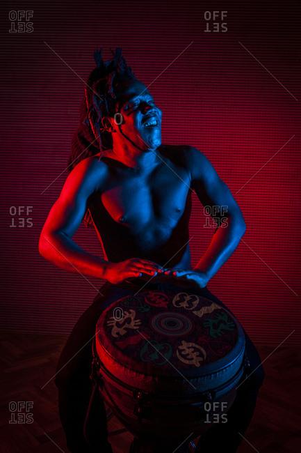 Young african rastafarian man enjoys rehearsing and plays tam tam