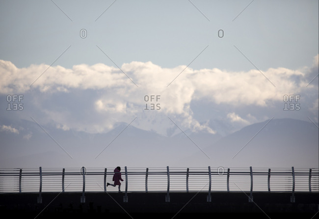 Girl running on Ogden Point breakwater, Victoria, British Columbia, Canada