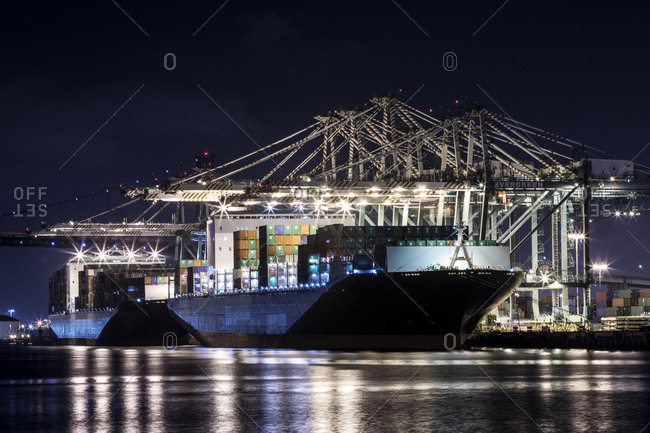 Los Angeles, California, USA - July 18, 2018: Ship loaded with cargo containers in a port with lights at night