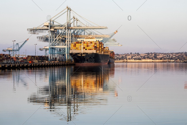Los Angeles, California, USA - July 19, 2018: Ship loaded with cargo containers reflected in the water at a seaport
