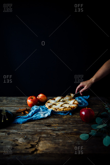 Person slicing into a whole apple pie with a pie server