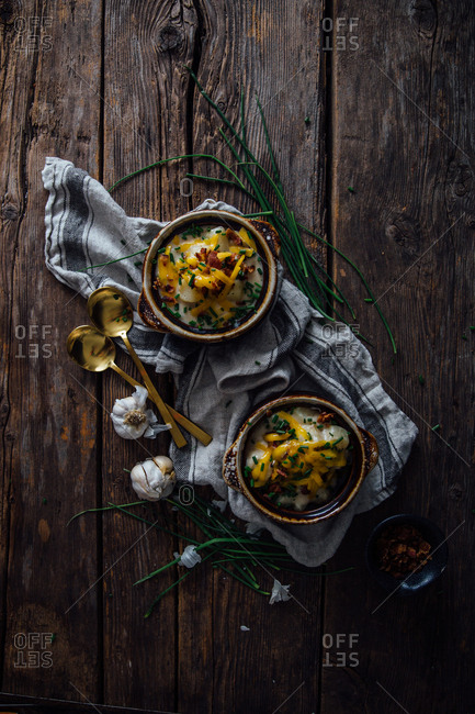 Two baked potato casseroles on a rustic wooden table with golden spoons