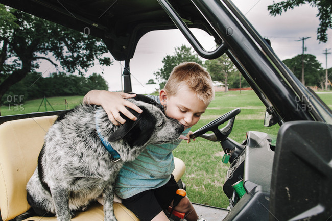 A boy petting a dog in a goat pen