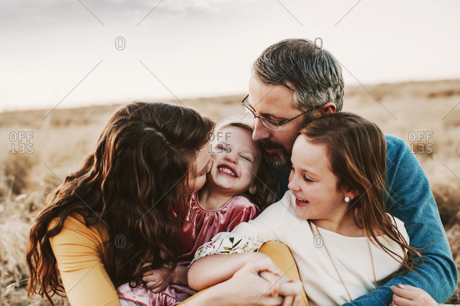 A family of four embracing