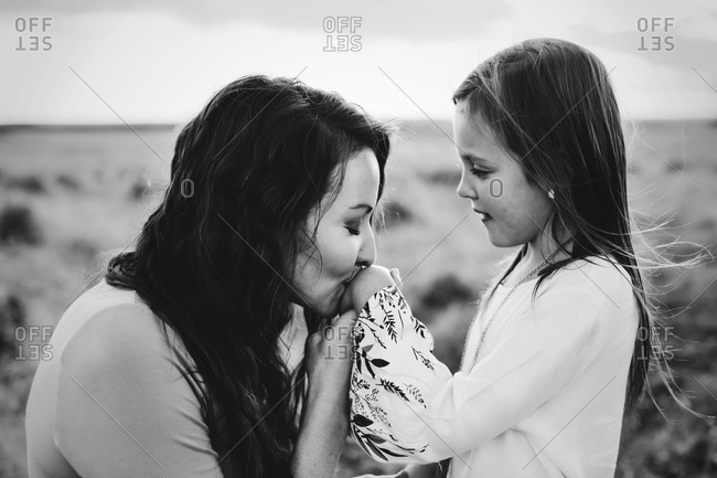 A mother kissing a girls hand