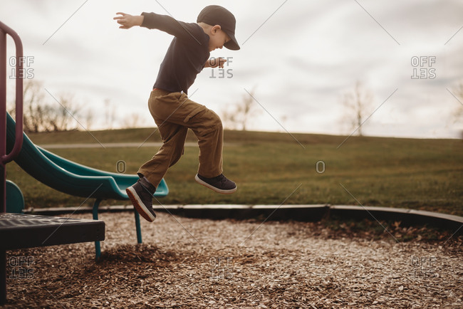 Young boy jumping from playground equipment