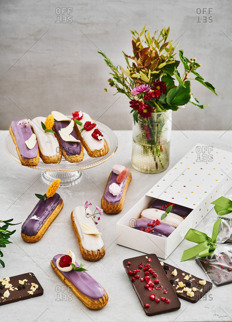 A variety of tasty eclairs and chocolate on a table