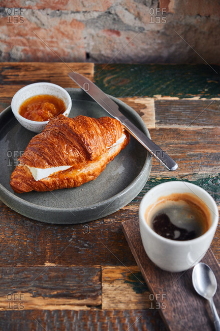 Coffee served with a croissant with brie cheese and jam