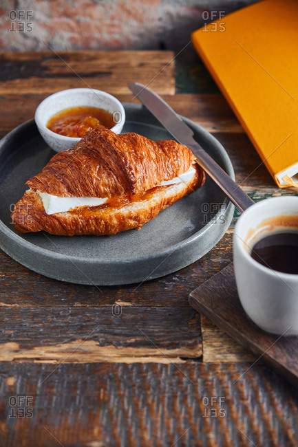 Croissant with brie cheese and jam served with coffee