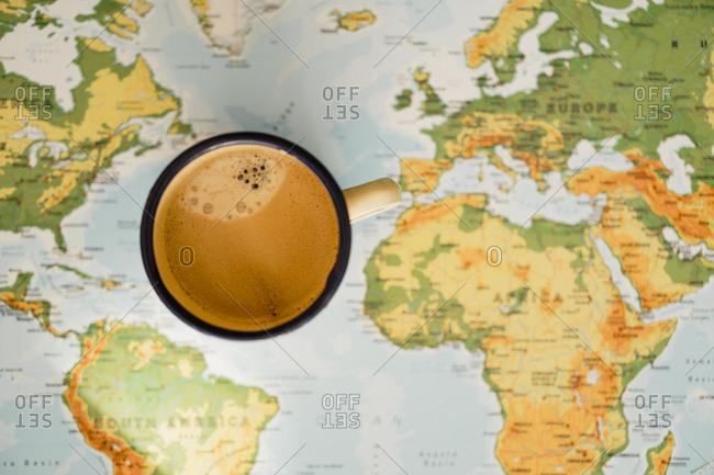 Metal coffee mug on top of world map