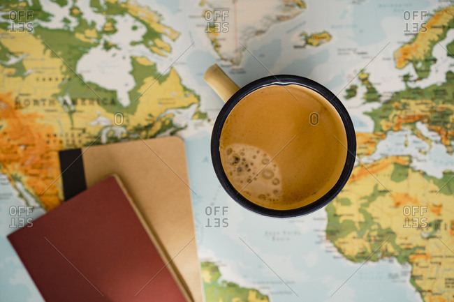 Metal coffee mug, passport and notebook on top of world map