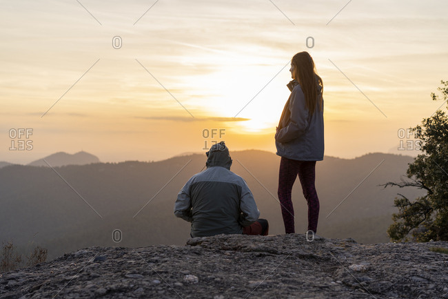 Man sitting and woman standing on top of hill looking at mountain sunset, Montserrat, Spain