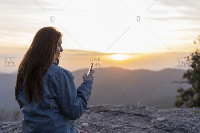 Young woman looking at phone on top of a hill during sunset