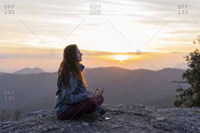 Young woman meditating on top of a mountain at sunset in Montserrat, Spain