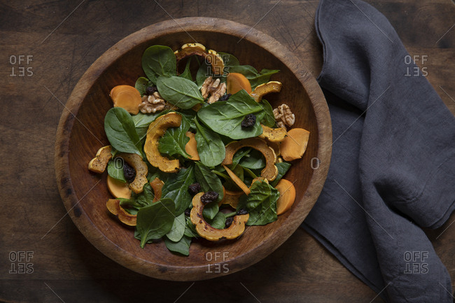 Delicata squash and spinach salad in wooden bowl
