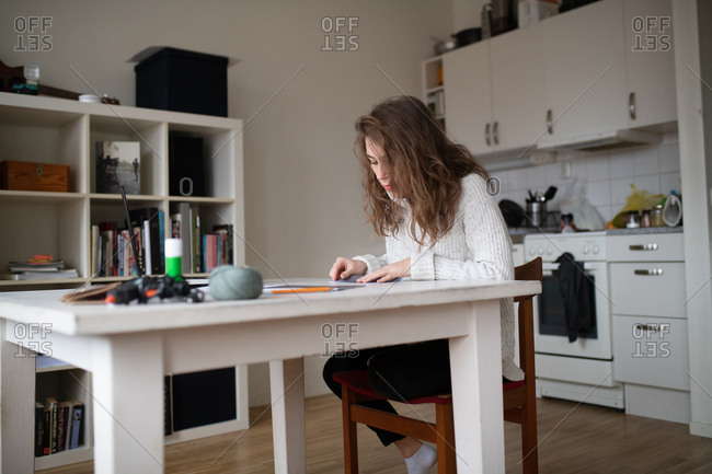Young woman sitting at a table working on a creative project at home