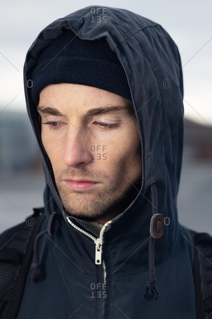 Portrait of a young man wearing a hooded jacket looking down