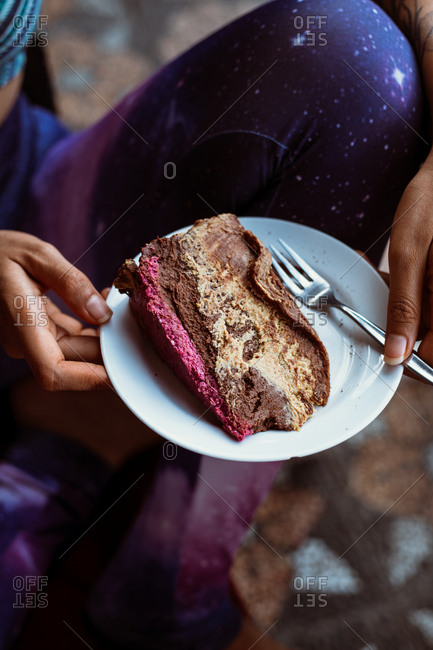 Person holding a plate with a slice of vegan chocolate cake