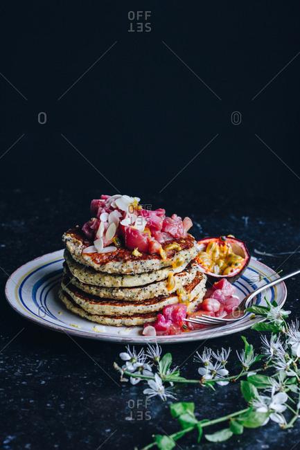 Stack of vegan pancakes topped with rhubarb