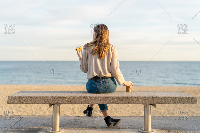 Young beautiful happy woman with coffee and doughnut sitting on bench in Barcelona beach, Catalonia, Spain