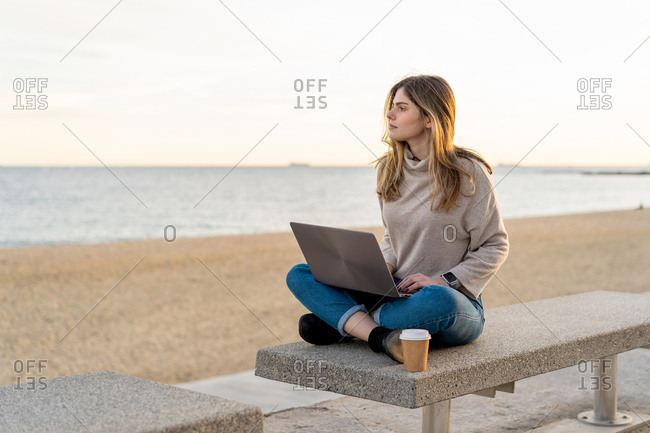 Young beautiful happy woman with coffee working with laptop on a bench in Barcelona beach, Catalonia, Spain