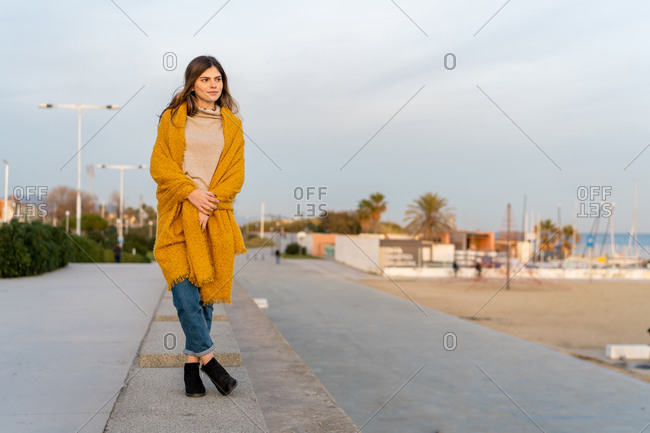 Young beautiful happy woman standing on bench in Barcelona beach, Catalonia, Spain