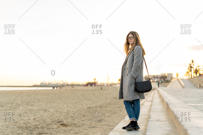 Young beautiful woman standing in boulevard during sunset Barcelona beach, Catalonia, Spain