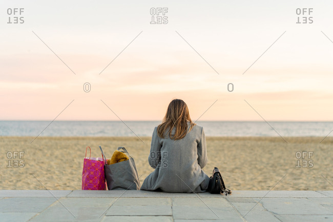 Back view of young beautiful happy woman sitting on floor in boulevard with shopping bags in Barcelona beach, Catalonia, Spain