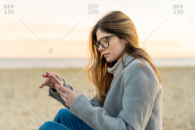 Young beautiful happy woman sitting on floor in boulevard using phone in Barcelona beach, Catalonia, Spain
