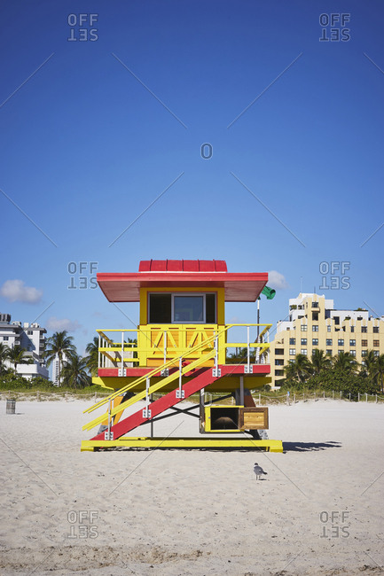 A red and yellow art deco lifeguard hut sits in the sand of South Beach, with buildings and a hedge row in the background