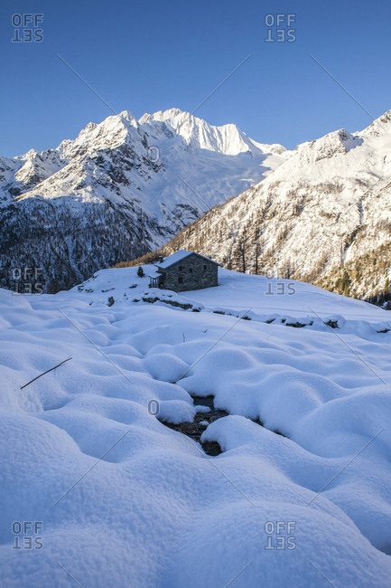 Stone hut at the foot of the snowy Monte Vazzeda, Alpe dell'Oro, Valmalenco, Valtellina, Sondrio province, Lombardy, Italy, Europe