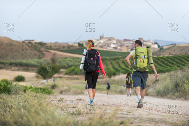 July 30, 2017: Pilgrims walking the Camino de Santiago (The Way of St. James) towards little village of Cirauqui, Navarre, Spain, Europe